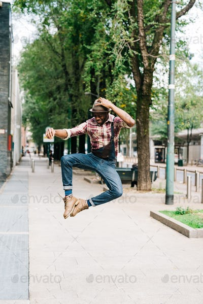 Young handsome afro back man jumping in the street of the city,