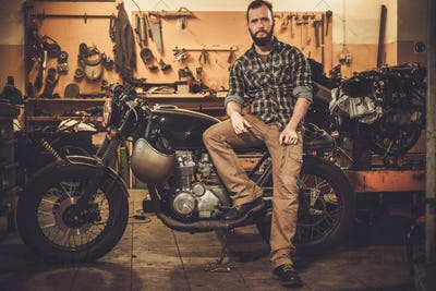 Rider and his vintage style cafe-racer motorcycle in customs garage