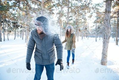 Joyful woman thowing snowballs in handsome man