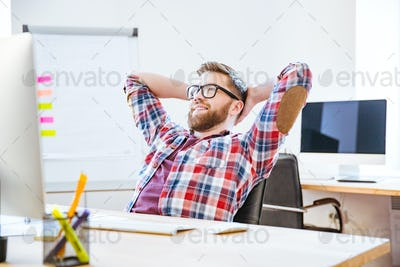 Happy man sitting with hands behind head and relaxing