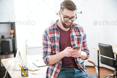 Cheerful young man sitting on the table and using smartphone