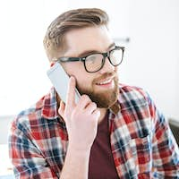 Happy man with beard in glasses talking on cell phone