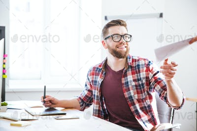 Happy designer using graphic pen tablet and taking documents