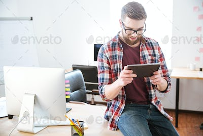 Smiling bearded man sitting with tablet on table in office