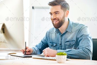 Happy male designer sitting and drawing on graphic tablet