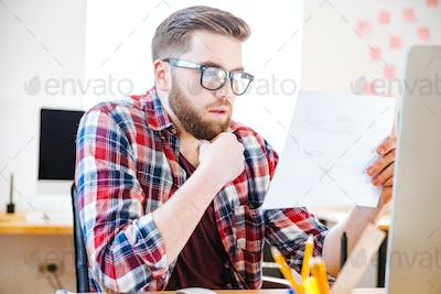 Serious man sitting and looking at blueprint in office