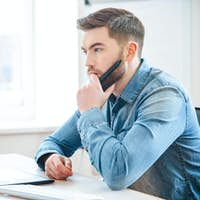 Pensive male designer thinking and making blueprints using pen tablet