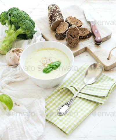 Broccoli cream soup with sunflower seeds, fresh basil and bread in bowl over white wooden table.