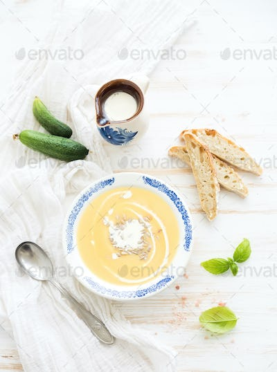 Pumpkin soup with cream, fresh basil, cucumbers and bread in vintage ceramic plate