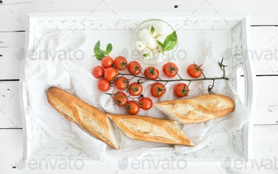 Baguette with branch of cherry-tomatoes, basil and mozzarella cheese