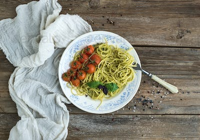 Pasta spaghetti with pesto sauce, basil, baked cherry-tomatoes on rustic wooden table