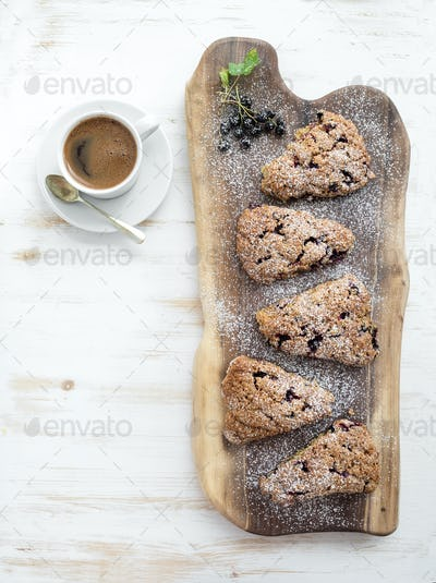 Fresh black-currant scones with cup of coffee , top view