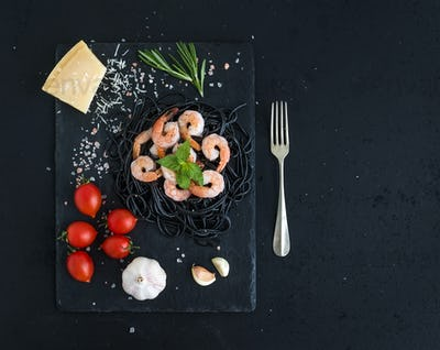 Black pasta spaghetti with shrimps, basil, pesto sauce, garlic, parmesan cheese