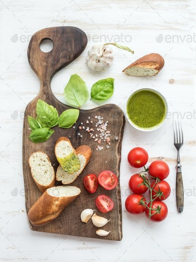 Pesto sauce, bread, cherry-tomatoes, fresh basil and garlic on rustic walnut chopping board
