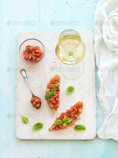 Tomato and basil bruschetta sandwich on white wooden serving board