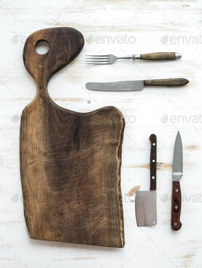 Kitchen-ware set. Old rustic chopping board made of walnut wood, knives, fork on a white background