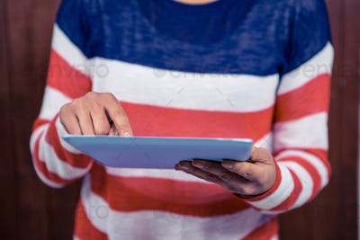 Mid section of woman using tablet against wooden wall