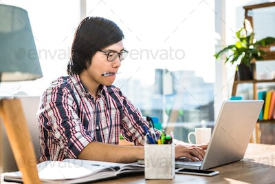 Hipster businessman with pen in mouth using laptop in office