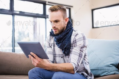 Handsome man using tablet on the couch in the living room