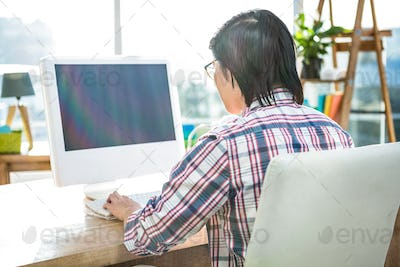 Rear view of businessman using computer in office