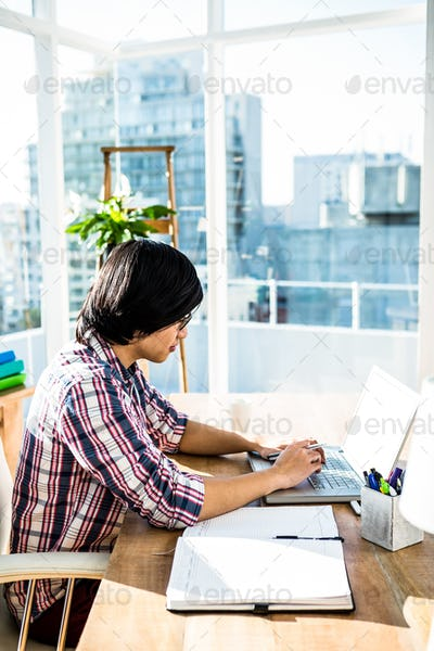 Serious hipster businessman using laptop in office
