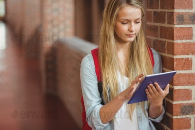 Student using tablet in the hallway at university