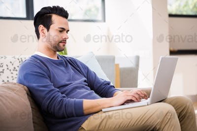 Handsome man using laptop on couch at home