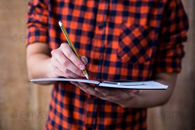 Hipster taking notes on notebooks on wooden background