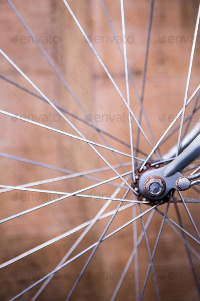 Close up view of spokes of wheel of a bike on wooden background