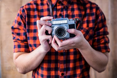 Hipster holding an old camera on wooden background