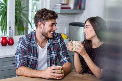 Happy couple having coffee together at home