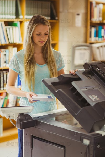 Smiling blonde student making a copy in library