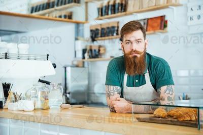 Portrait of bearded male barista standing in coffee shop