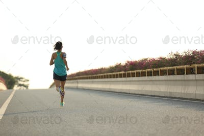 young fitness woman runner running on seaside bridge
