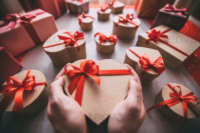 Male hands holding gift box heart.