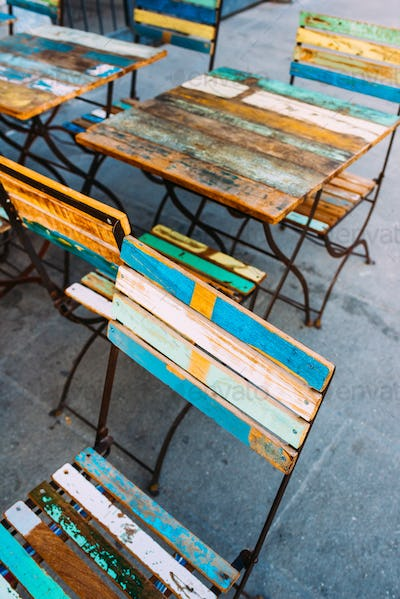 Close up on some colorful wooden chairs and table of a bar outdo
