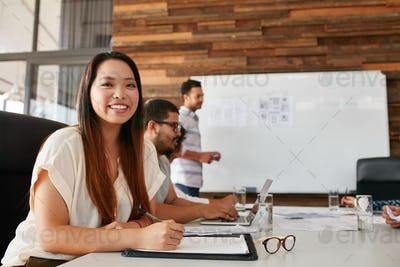 Asian woman smiling during business presentation