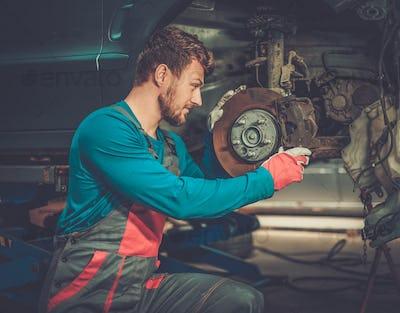 Mechanic checking car brake system in a workshop