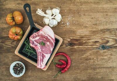 Raw fresh meat ribeye steak with pepper, salt, chili, garlic, heirloom tomatoes