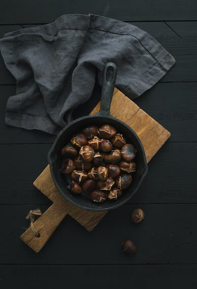Roasted chestnuts in iron skillet pan on rustic wooden board over black table background, top view.