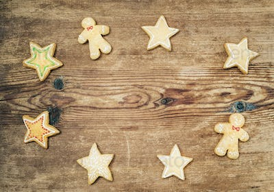 Christmas homemade gingerbread cookies of man and stars over rustic wooden background, top view