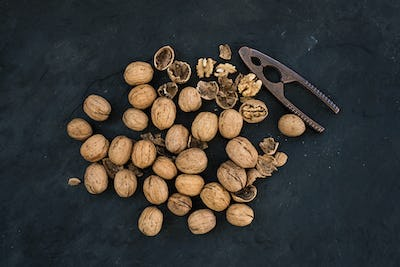 Walnuts with nutcracker over  black slate stone background