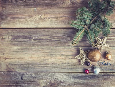 Christmas or New Year rustic wooden background with toy decorations and fur tree branch, top view