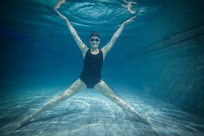 Pretty woman stretching underwater at the pool