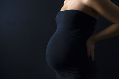 Beautiful pregnant woman with hands on her back