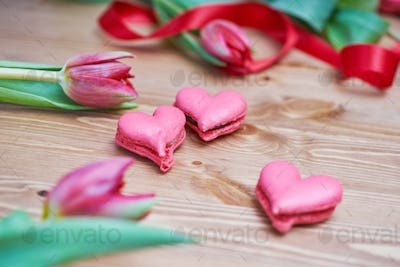 Heart-shaped macarons with flowers and ribbon on a wooden table.