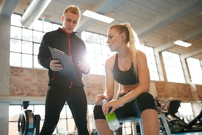 Personal trainer making an exercise plan for young woman