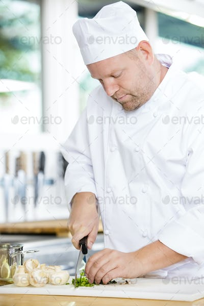 Professional chef preparing vegetables to a healthy dish