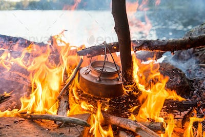 Making coffee on camp fire near water