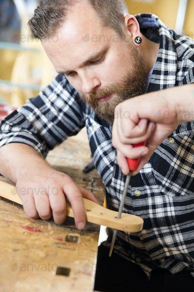 Close-up of craftsman files wooden guitar neck in workshop